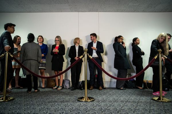 People wait in line outside the hearing room to attend Comey's testimony.