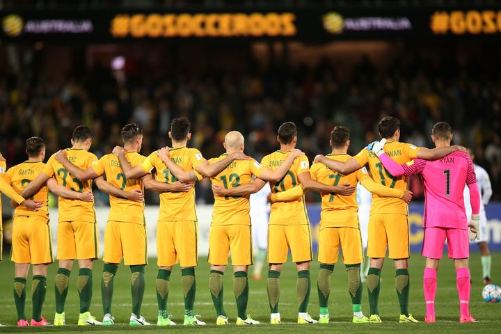 Australia's national team stands linked and at attention during the moment of silence.