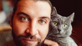 Mid adult man and cat looking at camera
