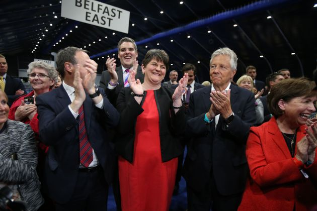 L-R: DUP deputy leader Nigel Dodds, leader Arlene Foster and former leader Peter Robinson cheer a DUP...