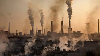 INNER MONGOLIA, CHINA - NOVEMBER 04: Smoke billows from a large steel plant as a Chinese labourer works at an unauthorized steel factory, foreground, on November 4, 2016 in Inner Mongolia, China. To meet China's targets to slash emissions of carbon dioxide, authorities are pushing to shut down privately owned steel, coal, and other high-polluting factories scattered across rural areas. In many cases, factory owners say they pay informal 'fines' to local inspectors and then re-open. The enforcement comes as the future of U.S. support for the 2015 Paris Agreement is in question, leaving China poised as an unlikely leader in the international effort against climate change. U.S. president-elect Donald Trump has sent mixed signals about whether he will withdraw the U.S. from commitments to curb greenhouse gases that, according to scientists, are causing the earth's temperature to rise. Trump once declared that the concept of global warming was 'created' by China in order to hurt U.S. manufacturing. ChinaÍs leadership has stated that any change in U.S. climate policy will not affect its commitment to implement the climate action plan. While the world's biggest polluter, China is also a global leader in establishing renewable energy sources such as wind and solar power. (Photo by Kevin Frayer/Getty Images)