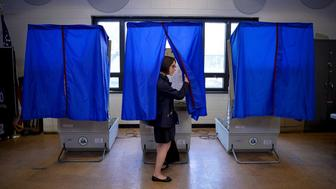 """A voter leaves the booth after casting her ballot in the Pennsylvania primary at a polling place in Philadelphia, Pennsylvania, U.S., April 26, 2016. Nearly half of Americans believe that the system that U.S. political parties use to pick their candidates for the White House is """"rigged"""" and two-thirds want to see the process changed, according to a Reuters/Ipsos poll.  REUTERS/Charles Mostoller/File Photo"""