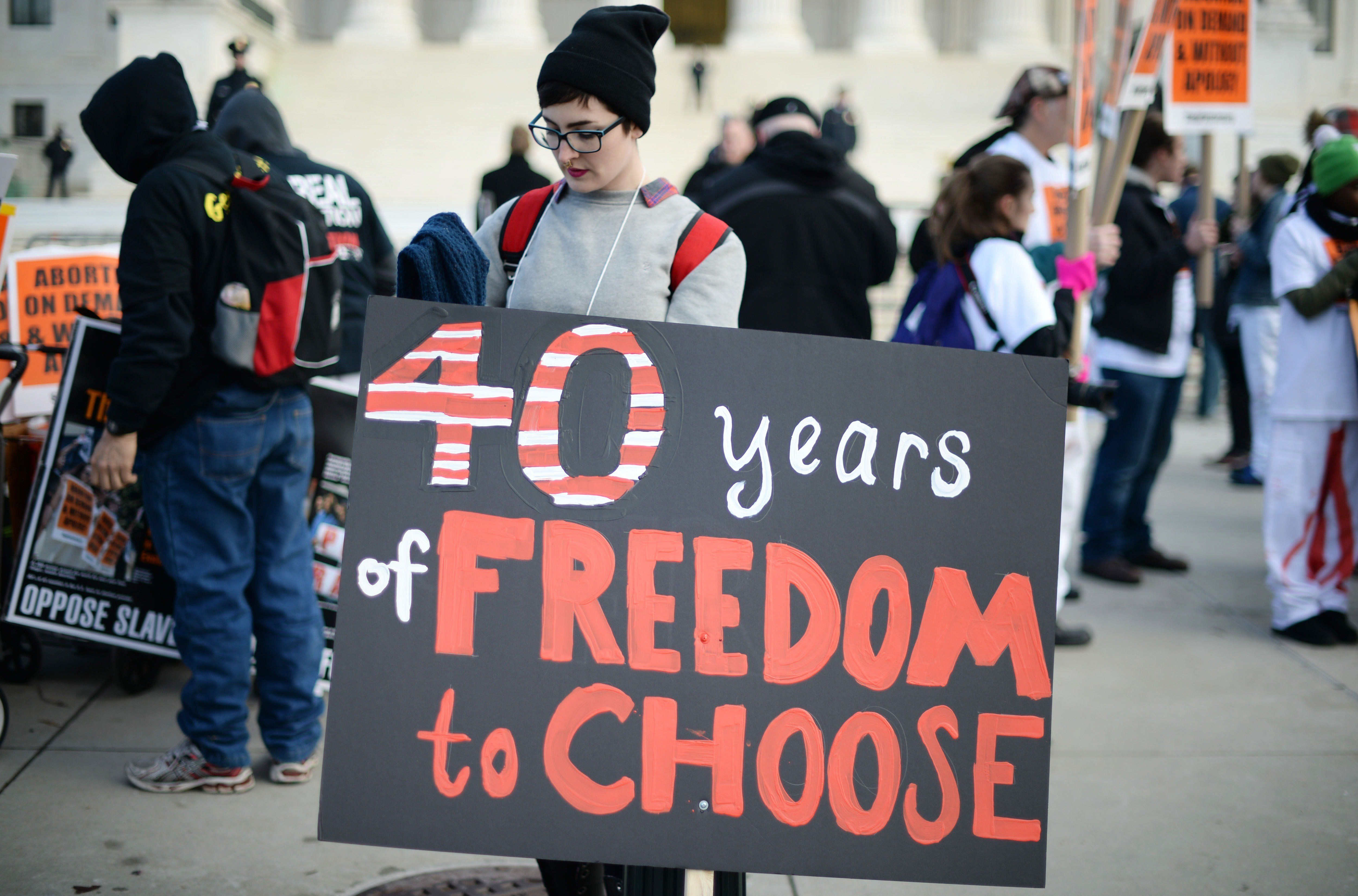 A pro-choice activists holds a placard in front of the US Supreme Court in Washington, DC, January 22, 2015, as she and others await the pro-choice activists with the March For Life. Tens of thousands of Americans who oppose abortion are in Washington for the annual March for Life, marking the 42nd anniversary of the Supreme Court's Roe v. Wade decision.          AFP PHOTO/JIM WATSON        (Photo credit should read JIM WATSON/AFP/Getty Images)