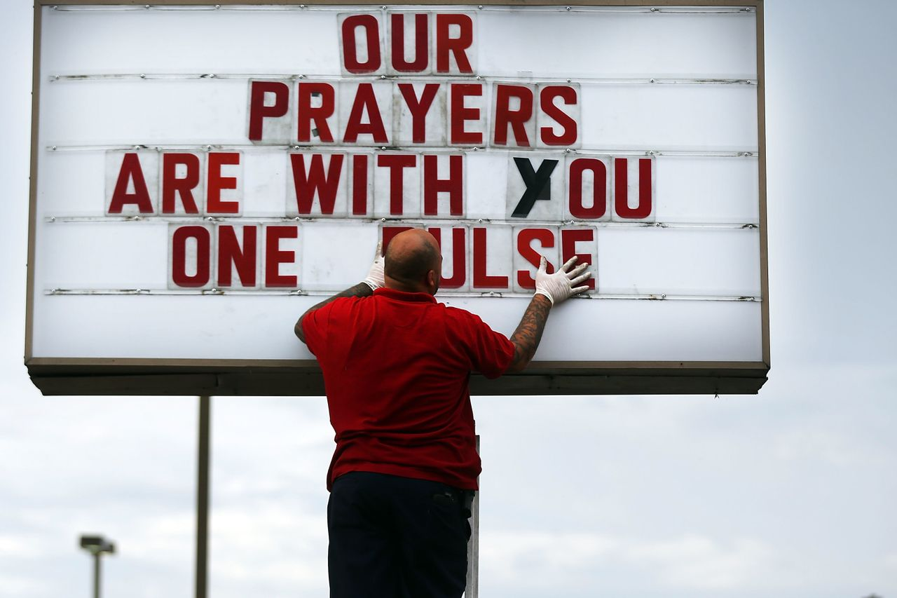 ORLANDO, FL - JUNE 16: Jiffy Lube employee Ralph Nieves put up a sign of support for the Orlando community following the shooting at the Pulse nightclub last Saturday night on June 16, 2016 in Orlando, Florida.