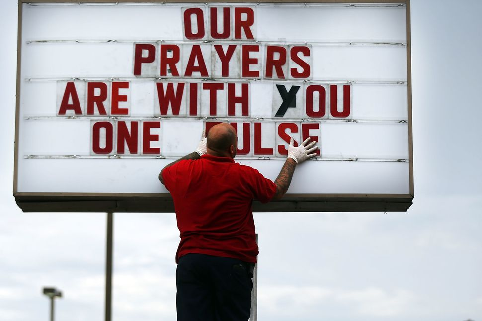 ORLANDO, FL - JUNE 16: Jiffy Lube employee Ralph Nieves put up a sign of support for the Orlando community following the shoo