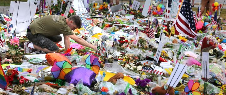 A visitor to the makeshift memorial for the victims of the Pulse massacre relights a candle after an afternoon rain shower at the Dr. Phillips Center for the Performing Arts in downtown Orlando, Fla., on Saturday, June 18, 2016.