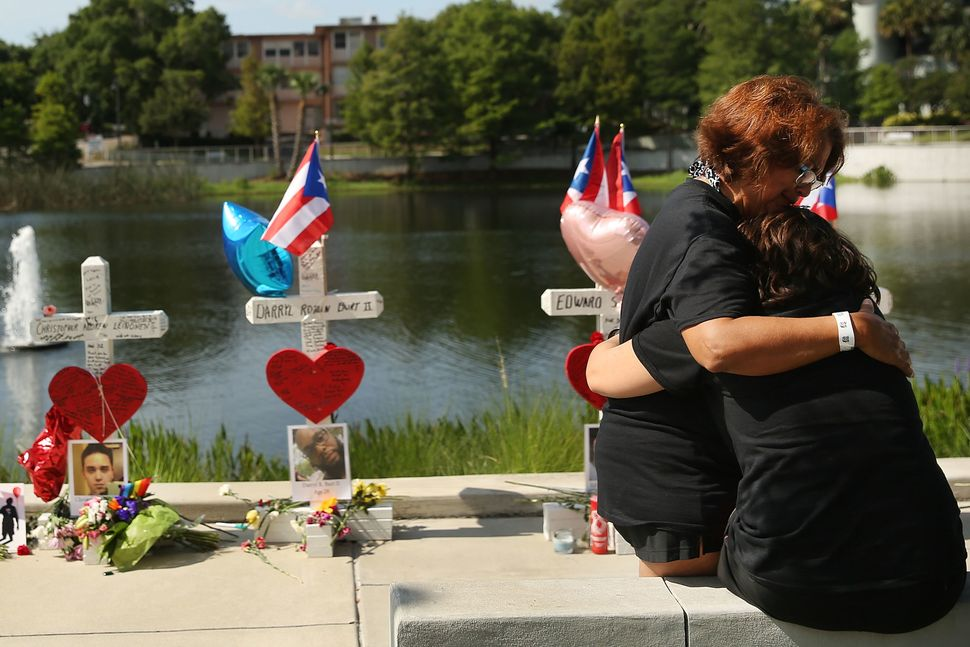 ORLANDO, FL - JUNE 18: Two women embrace beside a memorial down the road from the Pulse nightclub on June 18, 2016 in Orlando