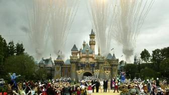 """Fireworks fill the sky as Mickey Mouse and other Disney characters fill the stage during the finale at Disneyland's 50th anniversary celebration ceremony at the Disneyland theme park, as """"The Happiest Homecoming on Earth"""" begins in Anaheim, California May 5, 2005. Sleeping Beauty Castle, background, is decorated in gold along with banners and five turret 'crowns' in honor of the anniversary. Walt Disney, founder of the Walt Disney Company and visionary behind the creation of Disneyland, opened the park on July 17, 1955. REUTERS/Fred Prouser  FP"""