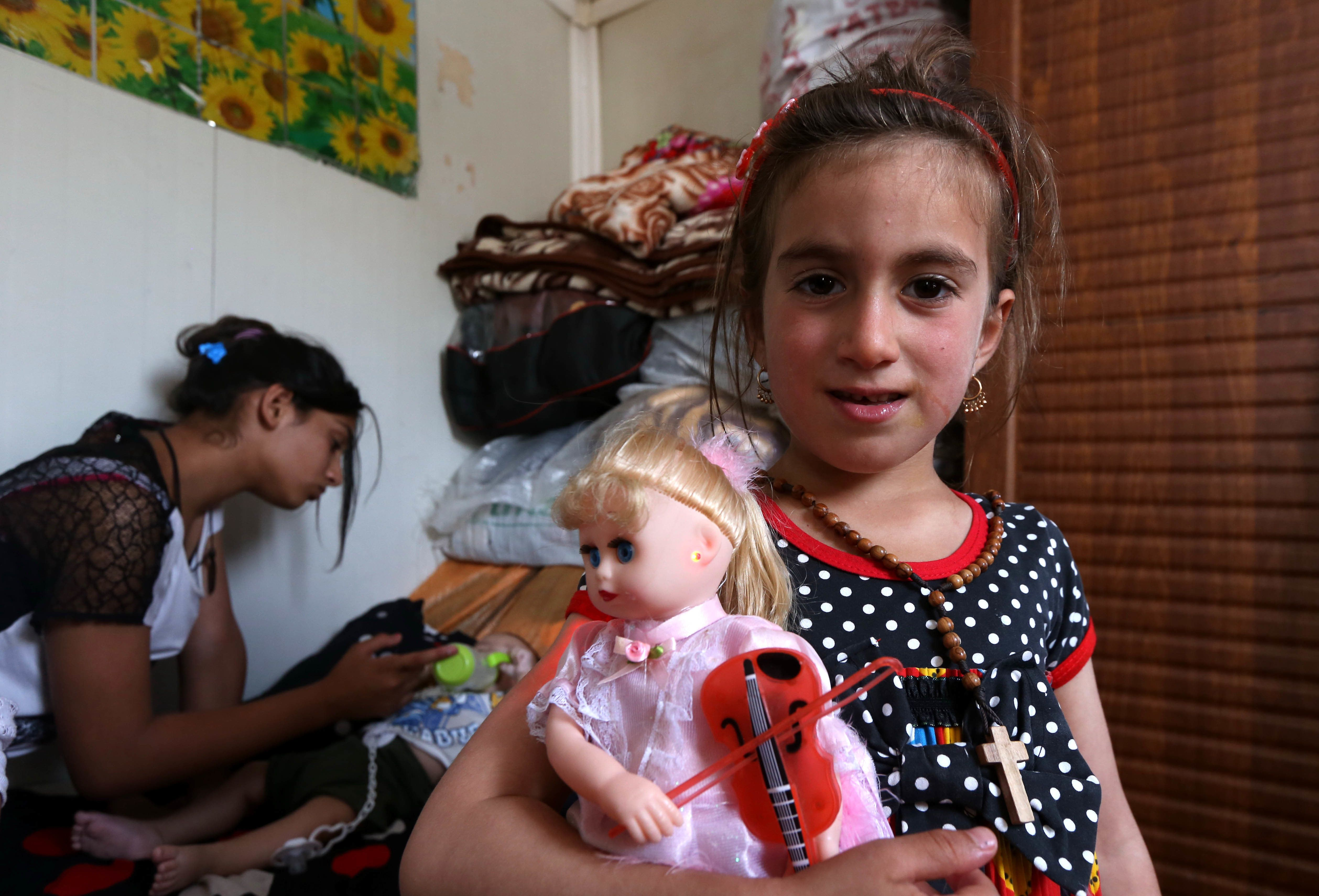 Christena, a 6-year-old Iraqi Christian girl, holds a doll during a meeting with her family at a camp for displaced Christian