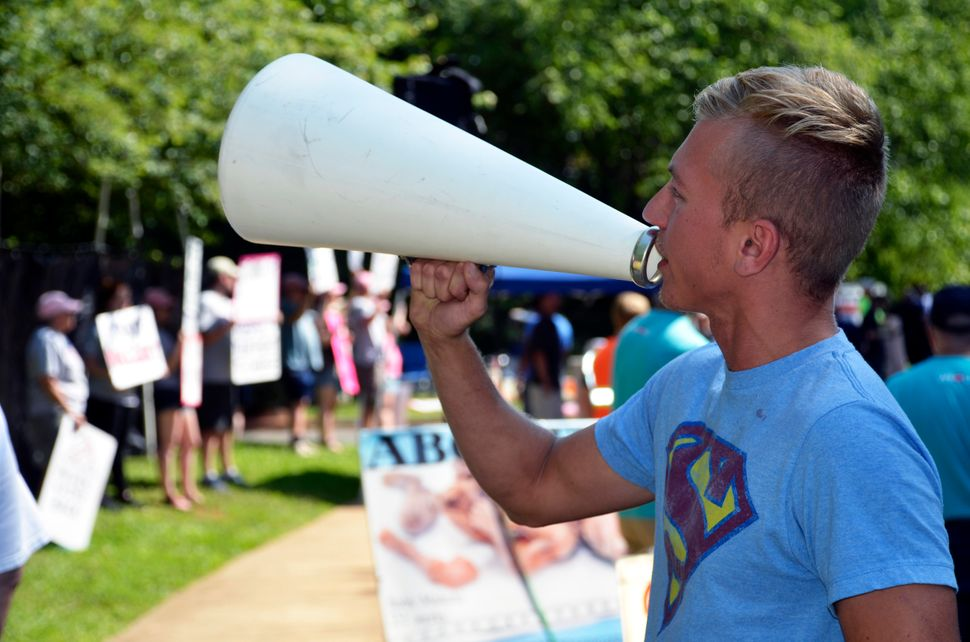"One anti-abortion protester uses a megaphone to yell outside the clinic. ""You're a coward,"" he said, to the male partner of a"