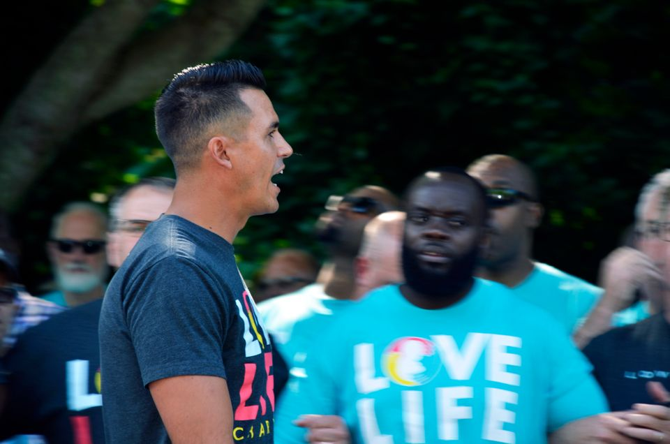 Love Live Charlotte founder Justin Reeder pumps up hundreds of men as they rally outside the