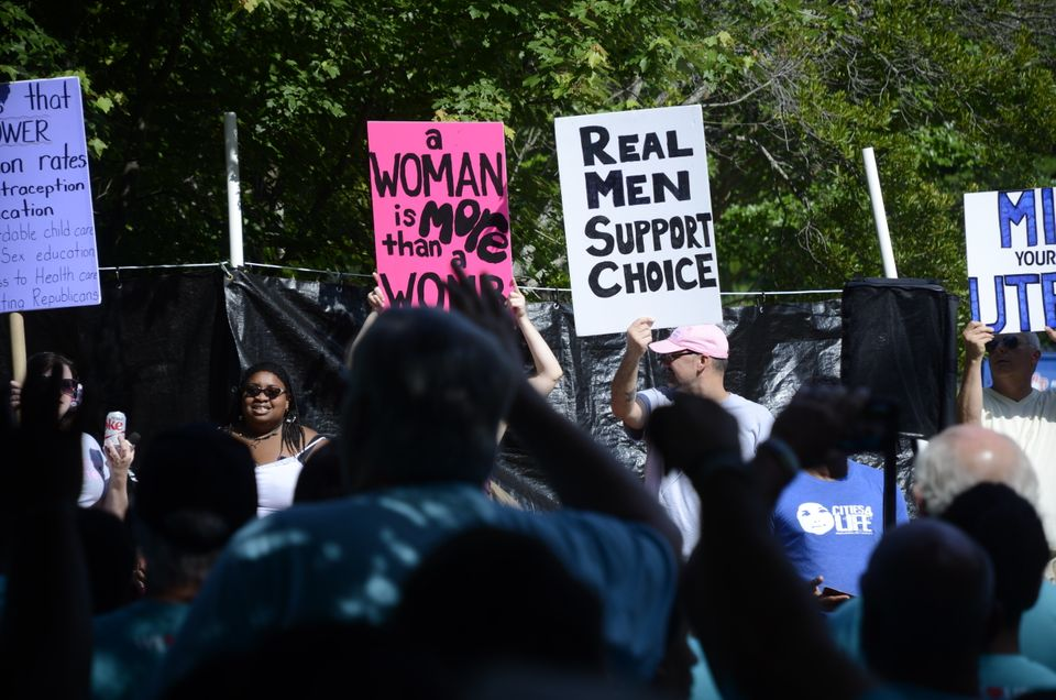 APWHC volunteer Jasmine Sherman, left, squares off with LLC protesters on