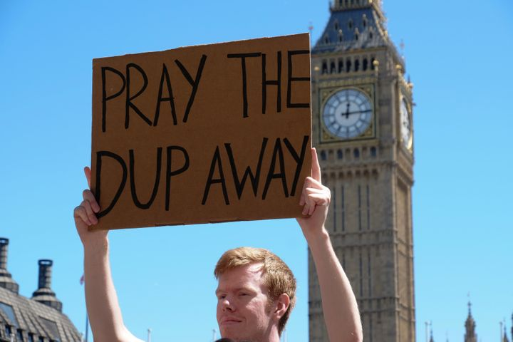 Protesters hold placards as they attend a demonstration against the Conservative party alliance with the DUP in Parliament Sq