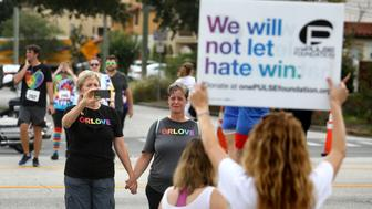 Pulse nightclub owner Barbara Poma holds up a sign for runners passing her club during the CommUNITYRainbowRun 4.9K road race on Saturday, June 10, 2017, in Orlando, Fla. The race is one of many events across central Florida commemorating the one-year anniversary of the June 12, 2016, massacre that killed 49 at Pulse. (Joe Burbank/Orlando Sentinel/TNS via Getty Images)