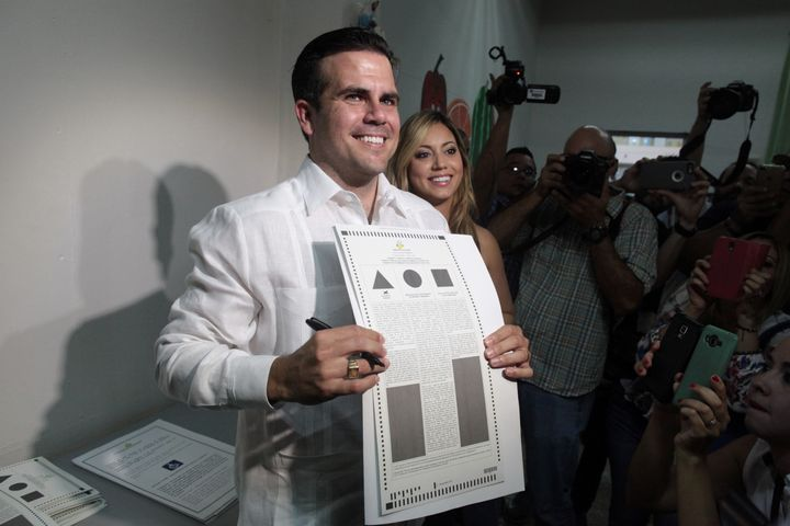Puerto Rico Governor Ricardo Rossello (C) shows his ballot paper next to his wife Beatriz Rossello as Puerto Ricans head to t