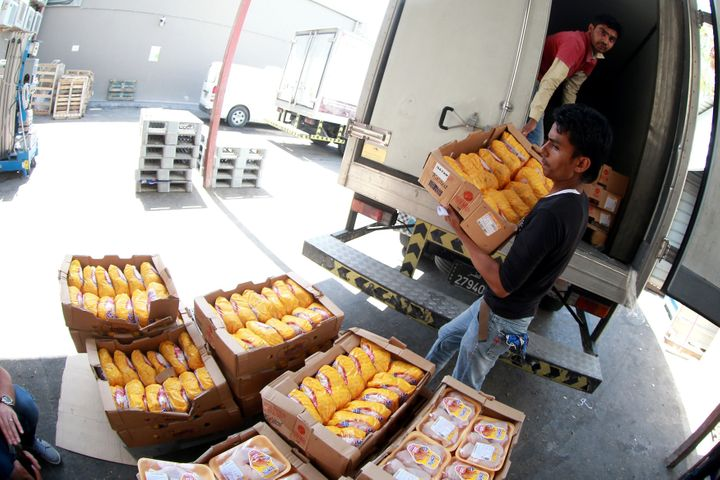 A man unloads chicken products at Al Meera market in Doha, Qatar, on Friday after people rushed grocery stores in fear o