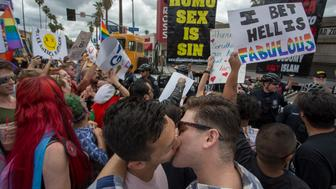 LOS ANGELES, CA - JUNE 11: Men kiss in defiance of a counter protest from provocative street preachers at the #ResistMarch during the 47th annual LA Pride Festival on June 11, 2017, in the Hollywood section of Los Angeles and West Hollywood, California. Inspired by the huge women's marches that took place around the world following the inauguration of President Donald Trump and by the early pride demonstrations of the 1970s, LA Pride replaced its decades-old parade with the #ResistMarch protest to promote human rights by marching from Hollywood to West Hollywood.  (Photo by David McNew/Getty Images)