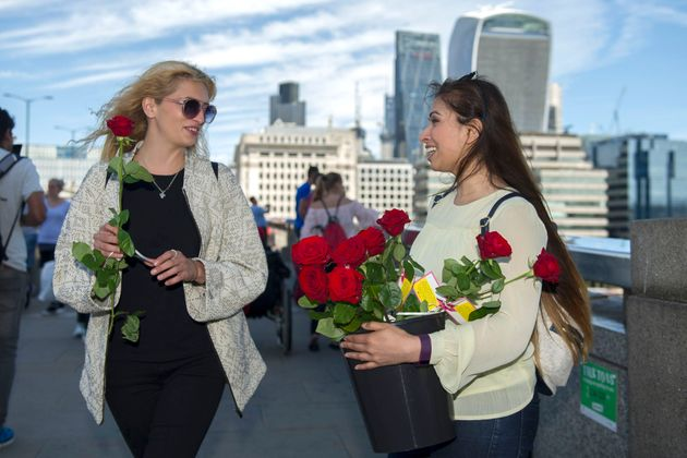 Roses with messages are given out to passers-by on London