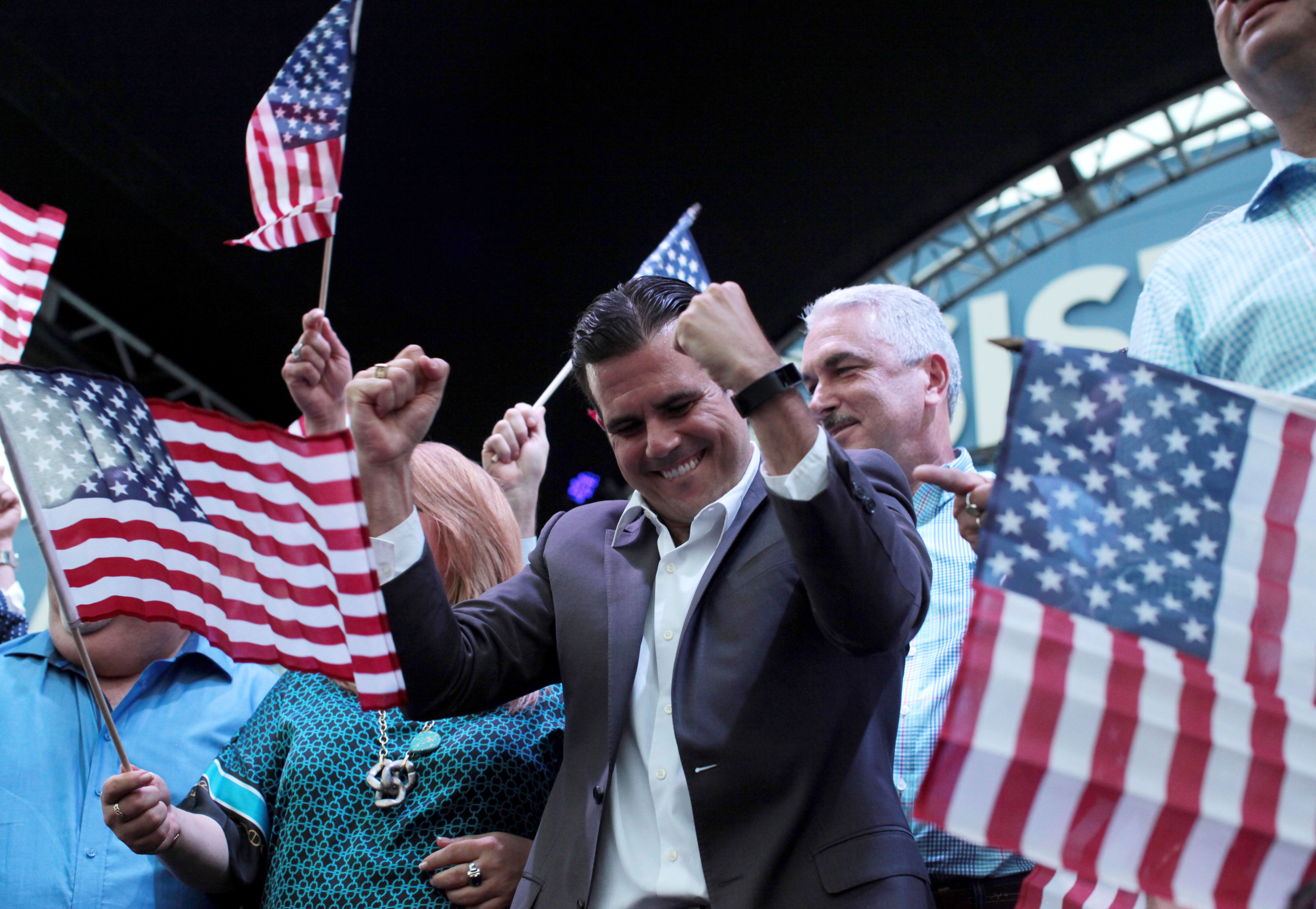 Puerto Rico Governor Ricardo Rosello (C) celebrates after the economically struggling U.S. island territory voted overwhelmingly on Sunday in favour of becoming the 51st state, in San Juan, Puerto Rico June 11, 2017. REUTERS/Alvin Baez     TPX IMAGES OF THE DAY