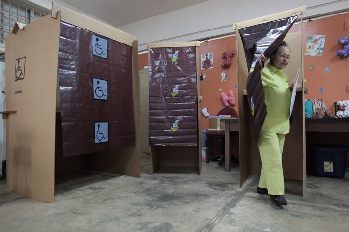 A woman leaves a voting booth as Puerto Ricans headed to the polls on Sunday to decide whether they want their struggling U.S