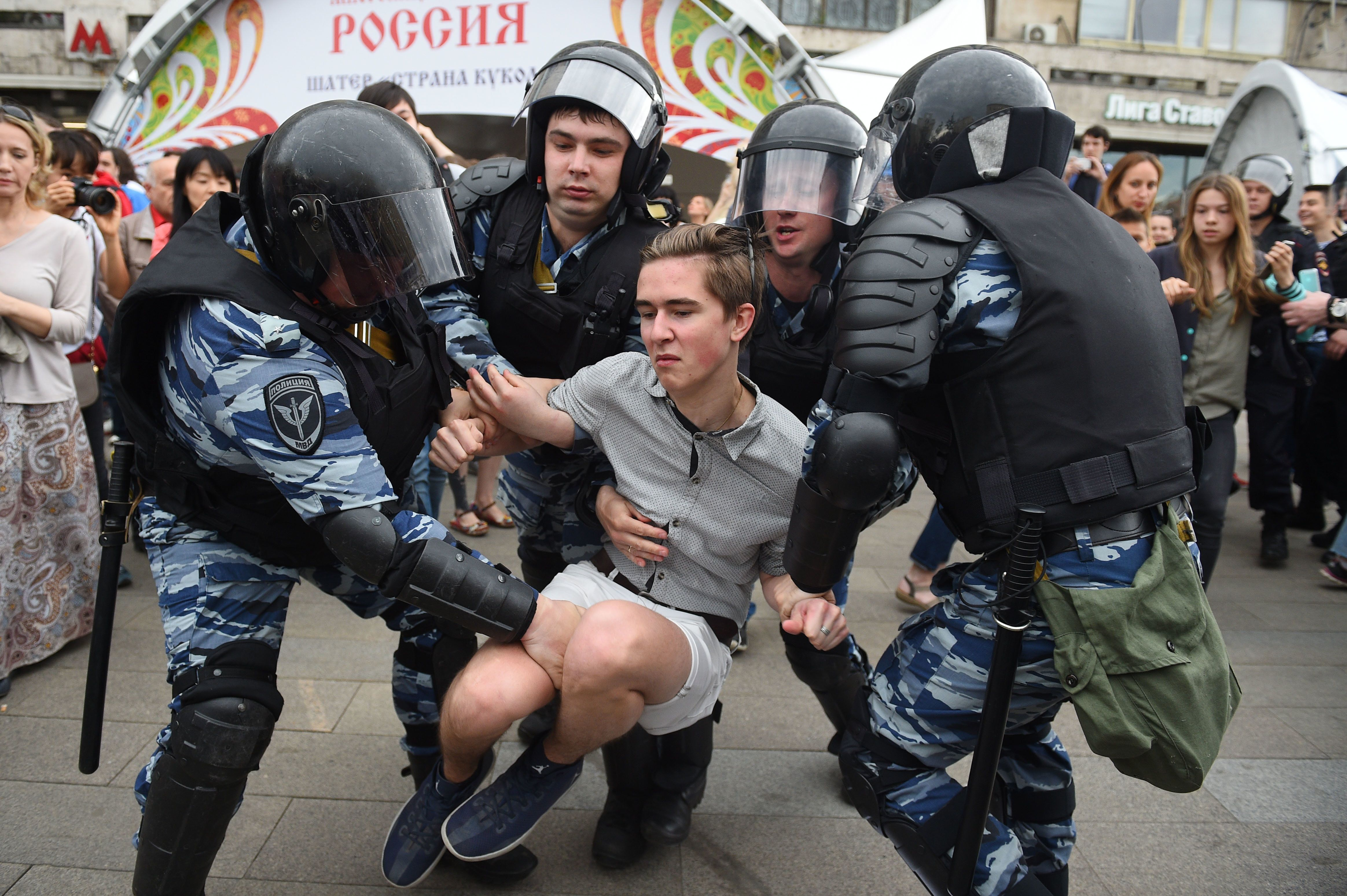 Russian police officers detain a participant of an unauthorized opposition rally in Tverskaya street in central Moscow on June 12, 2017.  Over 200 people were detained on June 12, 2017 by police at opposition protests called by Kremlin critic Alexei Navalny, said a Russian NGO tracking arrests. 'About 121 people were detained in Moscow up to this point. In Saint-Petersburg - 137,' OVD-Info group, which operates a detention hotline, wrote on Twitter.  / AFP PHOTO / STR        (Photo credit should read STR/AFP/Getty Images)