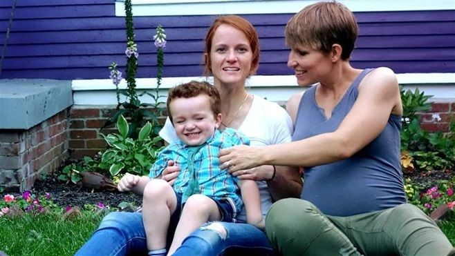 Jennifer and Nicole Singley sit with their son, Huck. The couple is one of several suing the state of Indiana to allow both m