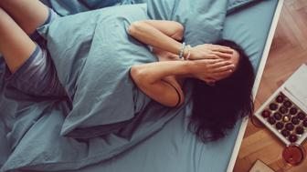 Depressed woman in bed with hands on face