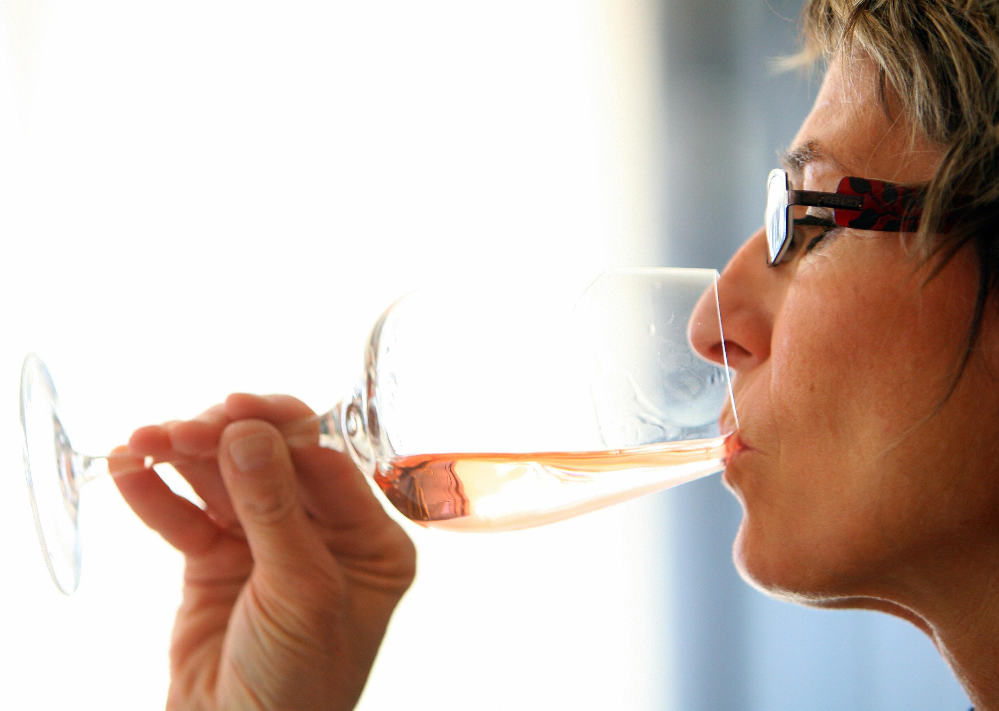 Une personne déguste du vin rosé, le 25 avril 2009, à Cannes à l'occasion du 6ème Mondial du Rosé organisé par l'union des oenologues de France du 25 au 27 avril 2009. Cette dégustation, exclusivement reservéé aux vins rosés issus de toutes les régions viticoles du monde, devrait proposer plus de 786 vins en provenance de 28 pays. Dégustés à l'aveugle par un jury représentant 18 nationalités, ces vins concourent pour une médaille d'or ou d'argent. La Commission européenne a repoussé récemment de près d'un mois au 19 juin l'adoption de nouvelles pratiques oenologiques, dont l'autorisation contestée par la France de fabriquer du vin rosé en coupant du rouge avec du blanc. AFP PHOTO STEPHANE DANNA (Photo credit should read STEPHANE DANNA/AFP/Getty Images)