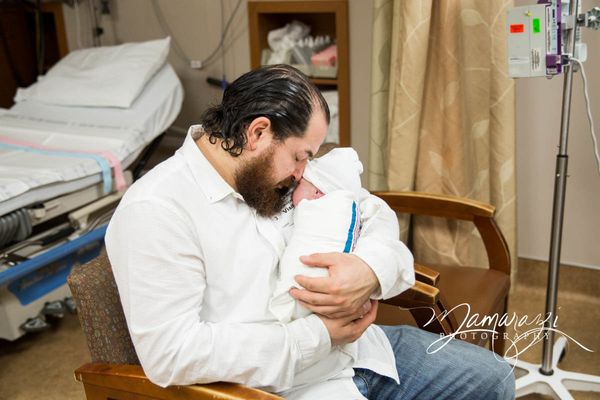 """""""This is one of my favorite images. The mom was in recovery after her C-section, so the dad spent some time snuggling and get"""
