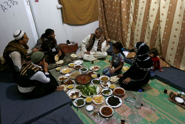 Abu Rustom, founder of a Syrian refugee folklore troupe eats Iftar with his family and troupe members,...