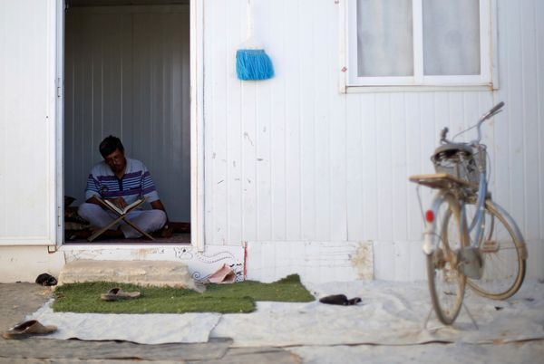 A Syrian refugee man reads the Koran inside his home at the Al-Zaatari camp.