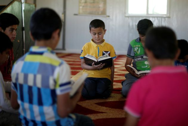 Syrian refugee boys read the Koran inside the Quran Memorization Center at the Al-Zaatari refugee camp...