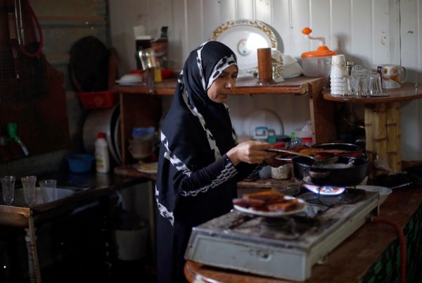 Aisha prepares Iftar food for her family and her husband's troupe members at the Al-Zaatari camp June 1.