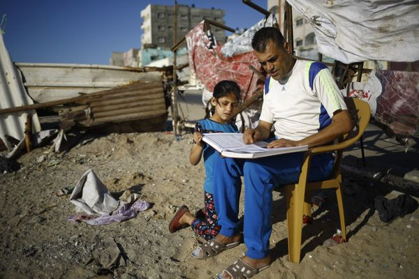 A Palestinian man reads a copy of the Koran, Islam's holiest book, with a young girl outside his home at Al-Shati camp in Gaz