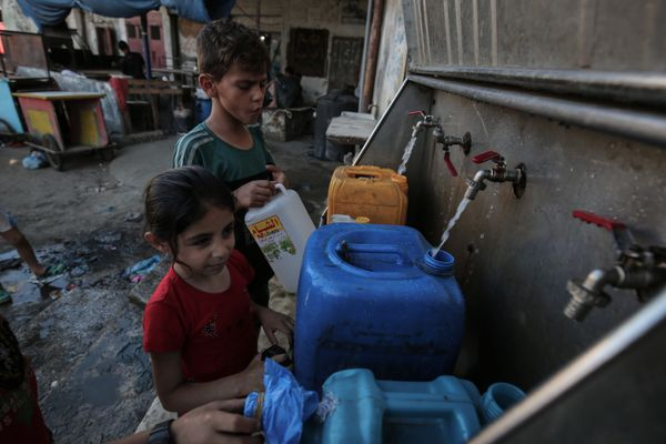 Palestinian children fill jerricans with drinking water from public taps during the Muslim holy month of Ramadan at the Rafah