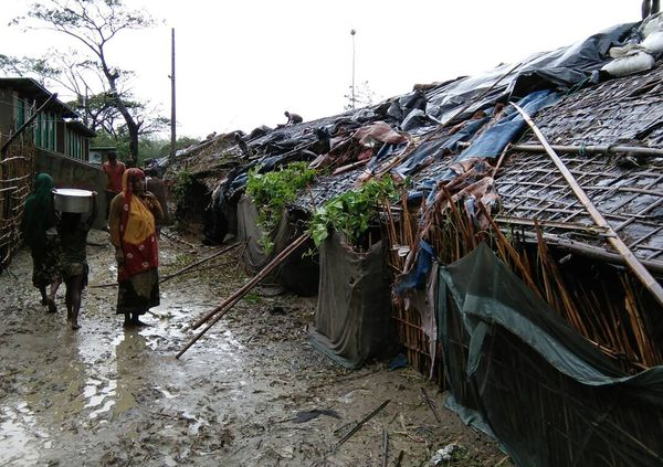 Rohingya refugees walk next to huts in a makeshift camp in Bangladesh's Cox's Bazar district on May 30, after Cyclone Mora ma