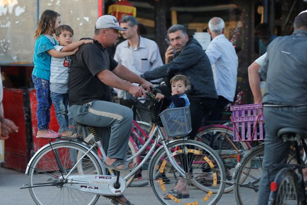 Syrian children ride a bicycle with their father at the main market, during the Muslim fasting month of Ramadan at the Al-Zaa