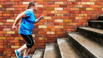 Young woman running up and down steps for exercise.