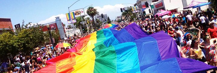 A large rainbow flag waves over a crowd.