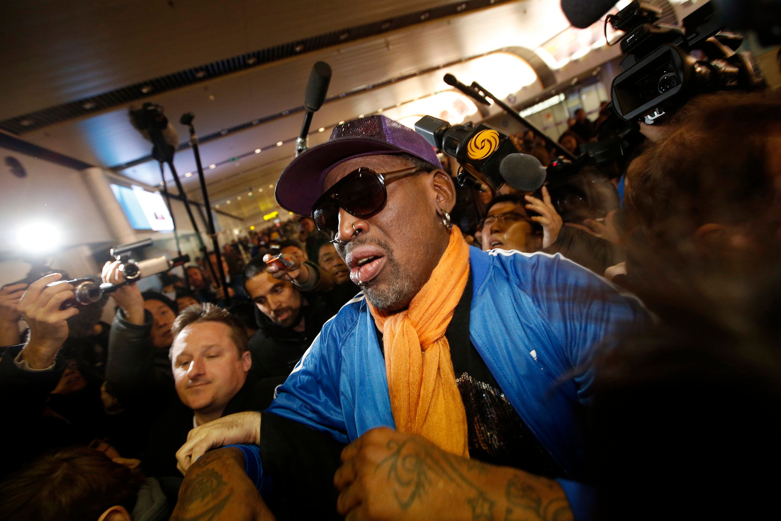Retired U.S. basketball star Dennis Rodman is surrounded by journalists upon his arrival from North Korea's Pyongyang at Beijing Capital International Airport January 13, 2014.  REUTERS/Kim Kyung-Hoon (CHINA - Tags: SOCIETY SPORT BASKETBALL TPX IMAGES OF THE DAY MEDIA)