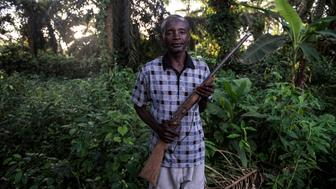 Jean-Marie Pongomoke poses with the gun he uses to hunt antelope with outside his village of Salambongo in the Congolese bush