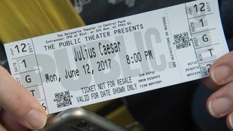 A woman holds her ticket to opening night of Shakespeare in the Park's production of Julius Caesar at Central Park's Delacorte Theater on June 12, 2017 in New York. A New York production of Shakespeare's 'Julius Caesar' drawing parallels between the assassinated Roman ruler and Donald Trump was in the eye of a growing storm, abandoned by corporate sponsors and sparking debate about freedom of expression. The play, which first opened in Central Park on May 23 and runs to June 18, has attracted right-wing outrage for similarities between the way Caesar is depicted and the Republican commander-in-chief, who is hugely unpopular in New York.  / AFP PHOTO / Bryan R. Smith        (Photo credit should read BRYAN R. SMITH/AFP/Getty Images)