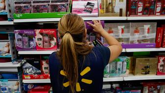 An employee arranges beauty product gift boxes displayed for sale at a Wal-Mart Stores Inc location ahead of Black Friday in Los Angeles California US on Monday November 24 2014 Retailers are planning to open earlier on Thanksgiving day this year in a bid to draw shoppers Wal-Mart Stores Inc is making Black Friday the shopping day after Thanksgiving a weeklong event this year