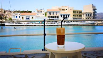 The frappe coffee in a glass with a straw on a coffee table with a view to the street and seaside. On a hot summer day in Agios Nikolaos, Crete island.