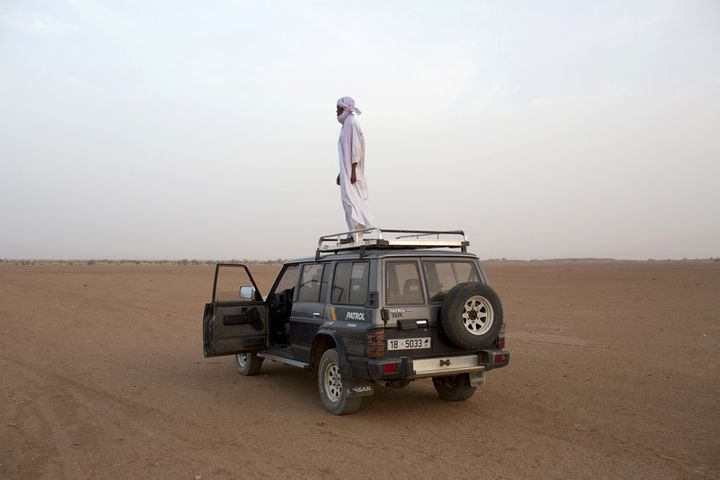 A human smuggler looks out for cars driven by his colleagues coming from Libya from the Niger in March 2014.