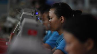 This photo taken on September 14, 2016 shows workers on a production line at the Huajian shoe factory, where about 100,000 pairs of Ivanka Trump-branded shoes have been made over the years amongst other brands, in Dongguan, in south China's Guangdong province. At the Dongguan factory, which employs some 15,000 people, it takes more than 200 workers to move a single pair of shoes from the concept stage to the loading dock. / AFP / GREG BAKER / TO GO WITH US-vote-Trump-China-manufacturing-employment,FOCUS by Ben Dooley          (Photo credit should read GREG BAKER/AFP/Getty Images)