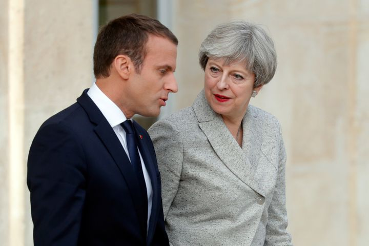French President Emmanuel Macron escorts Britain's Prime Minister Theresa May as they arrive to speak to the press at the Ely