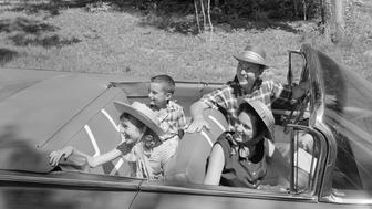 1960s FAMILY OF FOUR IN CONVERTIBLE AUTOMOBILE TOP DOWN LOOKING TOWARDS LEFT  (Photo by H. Armstrong Roberts/ClassicStock/Getty Images)