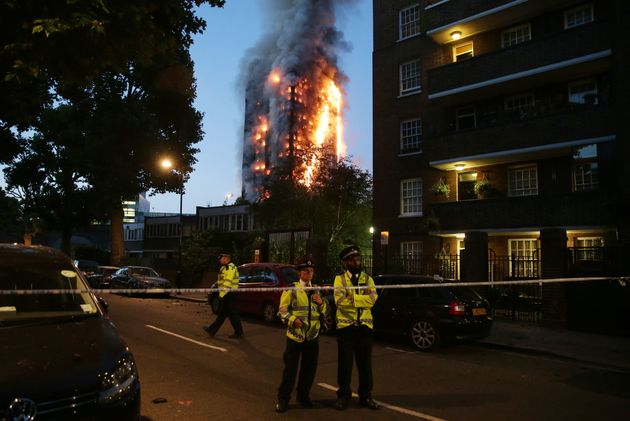 Police man a security cordon as a huge fire engulfs the Grenfell Tower in west