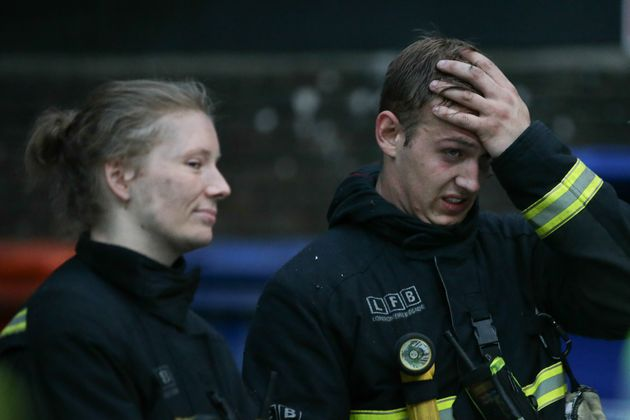 Firefighters react as they attend the